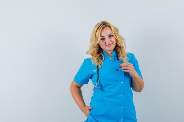 Kobieta lekarz patrząc na kamery ręką w kieszeni w niebieskim mundurze i patrząc zadowolony, miejsce na tekst