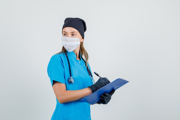 Kobieta lekarz patrząc wstecz podczas pisania w schowku w mundurze, rękawiczkach, masce i patrząc poważnie.