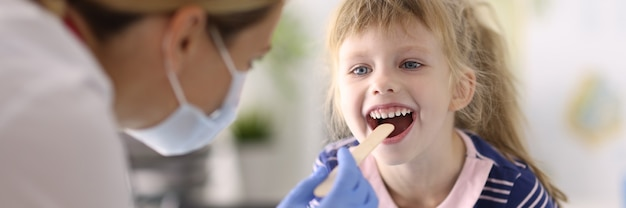 Kobieta lekarz pediatra w ochronnej masce medycznej i gumowych rękawiczkach bada gardło małej dziewczynki portret drewnianej szpatułki. badanie i leczenie dzieci w koncepcji pandemii covid 19.