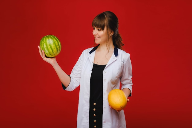 Kobieta lekarz pielęgniarka w białym fartuchu z owocami w dłoniach pozuje na czerwonym tle, melon, arbuz,