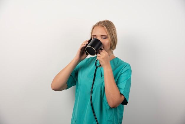 Kobieta lekarz pije herbatę na białym.