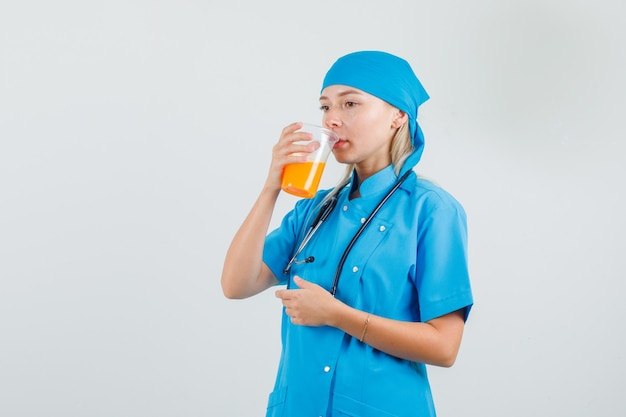 Kobieta lekarz pije sok owocowy myśląc w niebieskim mundurze