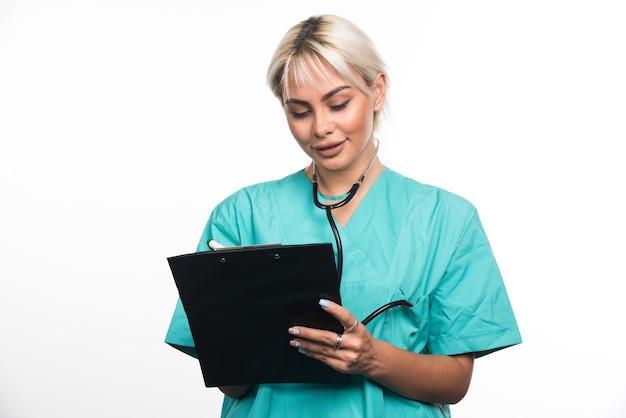Kobieta lekarz pisze coś w schowku za pomocą pióra na białej powierzchni