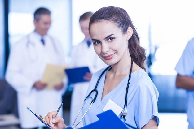 Kobieta lekarz pisze raport medyczny i kolegów stojących w tyle