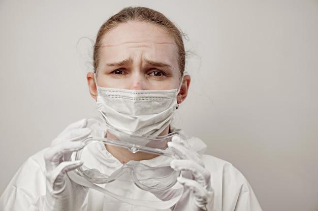 Kobieta lekarz po całodziennej pracy w szpitalu zdejmuje kombinezon ochronny, maskę i okulary.