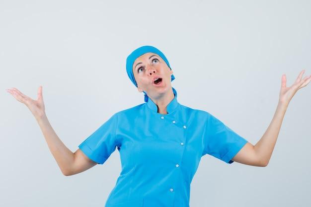 Kobieta lekarz podnosząc ręce, patrząc w niebieski mundur i patrząc zdumiony, widok z przodu.