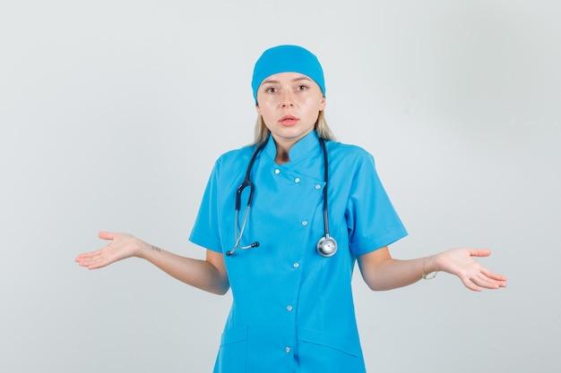 Kobieta lekarz pokazując bezradny gest w niebieskim mundurze i patrząc zdezorientowany.