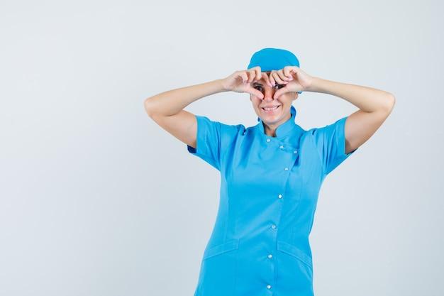 Kobieta lekarz pokazując gest serca w niebieskim mundurze i patrząc zadowolony, widok z przodu.