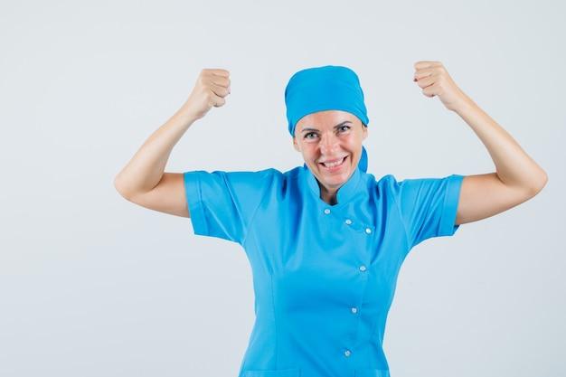Kobieta lekarz pokazując gest zwycięzcy w niebieskim mundurze i wyglądający na błogi. przedni widok.