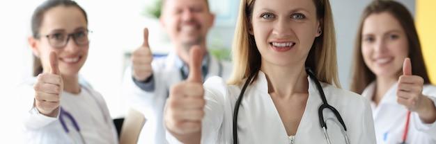 Kobieta lekarz pokazując kciuk do góry na tle kolegów