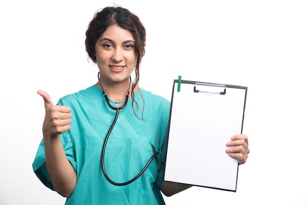 Kobieta lekarz pokazując kciuki do góry z pustym schowkiem na białym tle. wysokiej jakości zdjęcie