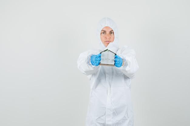 Kobieta lekarz pokazując model domu w kombinezonie ochronnym