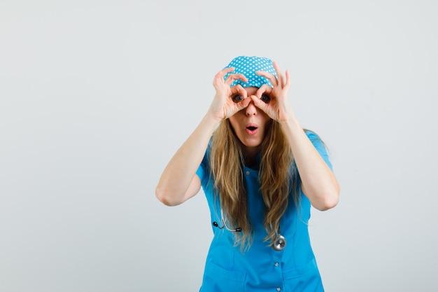 Kobieta lekarz pokazując okulary gest w niebieskim mundurze i patrząc zdziwiony