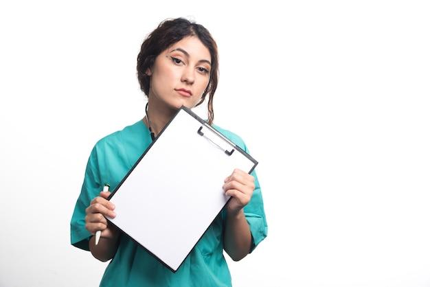 Kobieta lekarz pokazując pusty schowek z piórem i stetoskopem na białym tle. wysokiej jakości zdjęcie