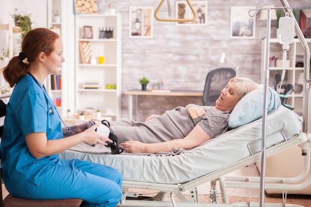 Kobieta lekarz pokazując starszy zestaw słuchawkowy kobieta vr w domu opieki.