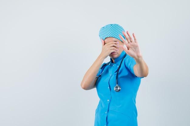 Kobieta lekarz pokazujący gest stop, zakrywający oczy w niebieskim mundurze i wyglądający na przestraszonego. przedni widok.