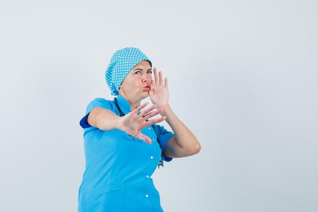 Kobieta lekarz pokazujący gest stopu z zamkniętymi ustami jako zamek błyskawiczny w niebieskim mundurze i wyglądający na przestraszonego, widok z przodu.