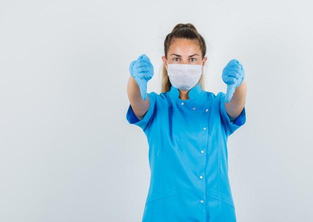 Kobieta lekarz pokazujący kciuki w dół w niebieskim mundurze, masce, rękawiczkach i niezadowolony.