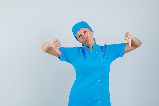 Kobieta lekarz pokazujący podwójne kciuki w dół w niebieskim mundurze i wyglądający na rozczarowanego, widok z przodu.