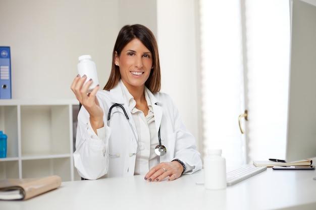 Kobieta lekarz pokazuje pigułki
