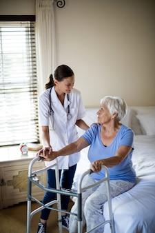 Kobieta lekarz pomaga starszej kobiecie chodzić z chodzikiem w domu