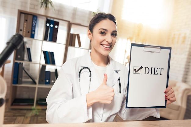 Kobieta lekarz posiada znak diety i pokazuje znak ok