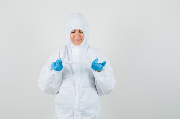 Kobieta lekarz posiadający maskę medyczną w kombinezon ochronny