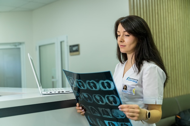 Kobieta lekarz posiadający obraz przepływu pracy mri mózgu w szpitalu diagnostycznym. koncepcja opieki zdrowotnej, rentgen, ludzie i medycyna.