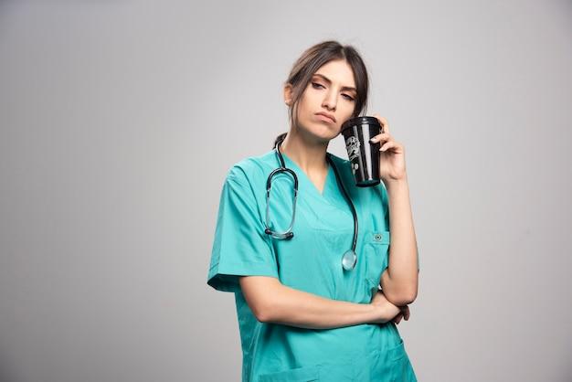 Kobieta lekarz pozowanie z filiżanką kawy na szaro
