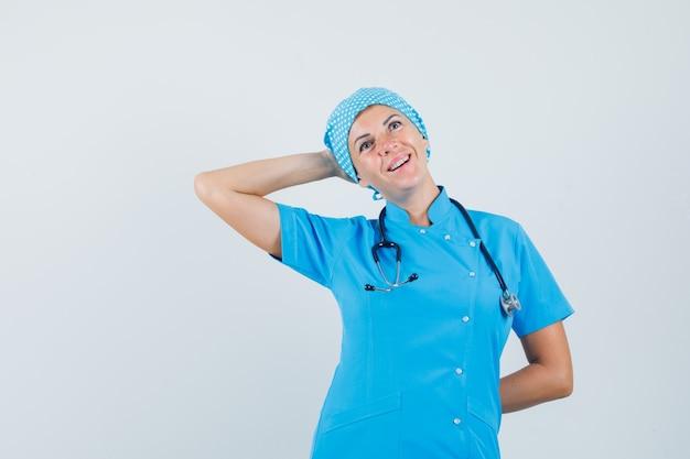 Kobieta lekarz pozowanie z ręką za głową w niebieskim mundurze i patrząc z nadzieją. przedni widok.