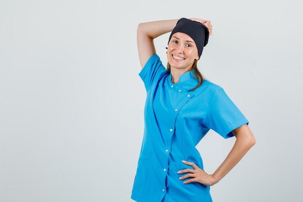 Kobieta lekarz pozowanie z rękami na głowie i talii w mundurze i patrząc wesoło