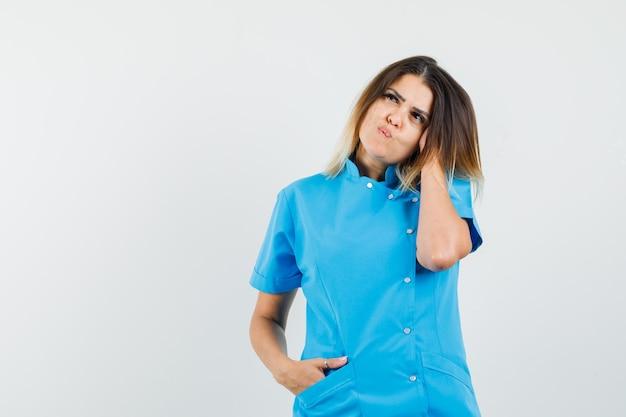 Kobieta lekarz pozuje myśląc w niebieskim mundurze i wygląda uroczo