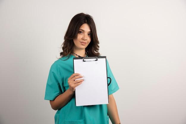 Kobieta lekarz pozuje ze schowkiem na białym
