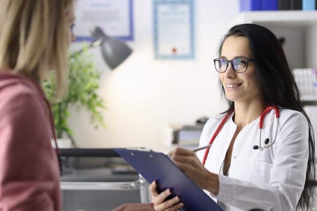 Kobieta lekarz prowadzi przyjmowanie pacjentów w koncepcji badania lekarskiego gabinetu
