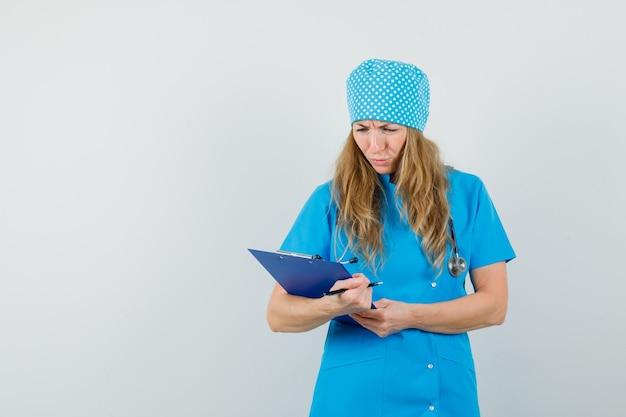 Kobieta lekarz przegląda notatki w schowku w niebieskim mundurze i wygląda na zmartwioną.