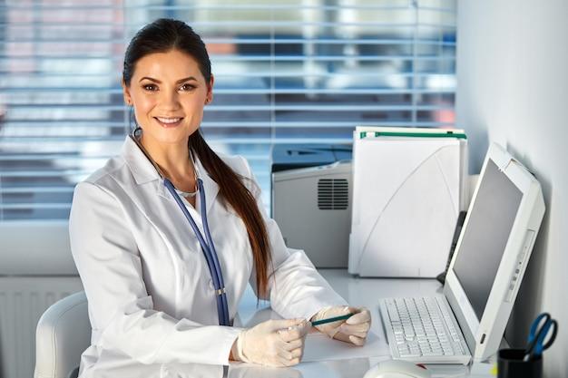 Kobieta lekarz przy użyciu komputera pc siedząc w miejscu pracy, jest miejscem pracy lekarza. koncepcja opieki zdrowotnej, ubezpieczeń i medycyny