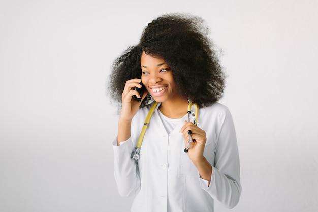 Kobieta lekarz przygotowanie sprzętu medycznego. żeński lekarz medycyny z stetoskopem w szpitalu na białym tle i opowiadać przez telefon