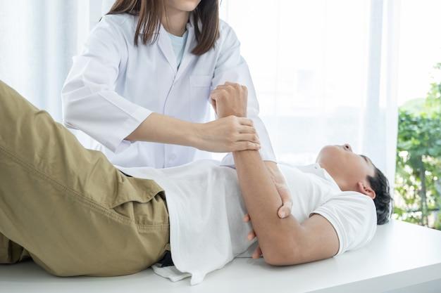 Kobieta lekarz ręce robi fizykoterapii poprzez rozszerzenie ramienia pacjenta płci męskiej.