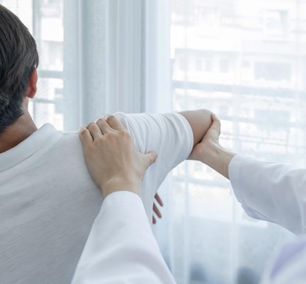 Kobieta lekarz ręcznie robi fizykoterapii przez rozszerzenie ramienia mężczyzny pacjenta.