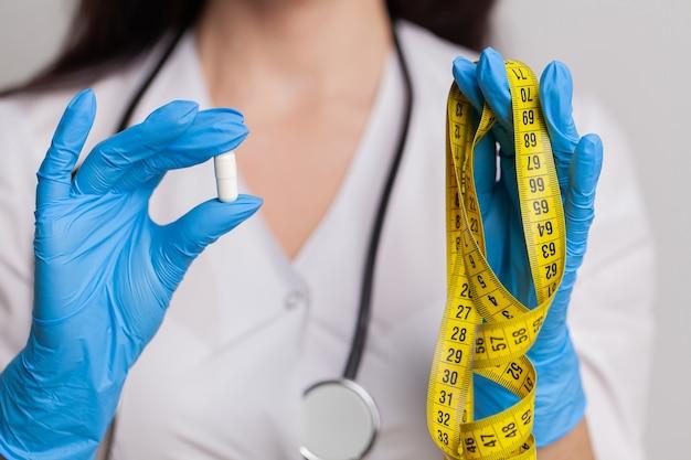 Kobieta lekarz ręka pokazuje jedną kapsułkę.