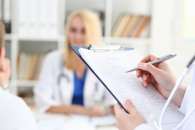 Kobieta lekarz ręka trzyma srebrne pióro wypełnianie listy pacjentów na zbliżenie pad schowka