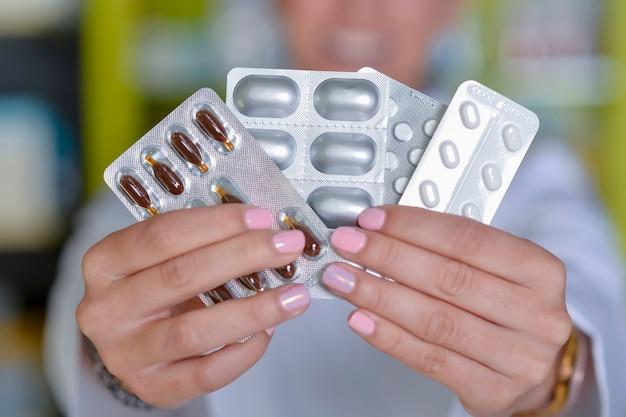 Kobieta lekarz ręka trzymać paczkę różnych pęcherzy tabletek w miejscu pracy.