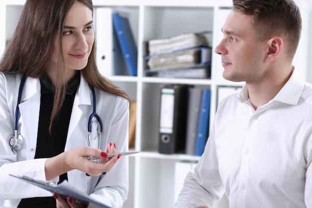 Kobieta lekarz ręka trzymać srebrny długopis i pokazując podkładkę. fizyczna zgoda formularza podpis oddział zapobiegania chorobom okrągły odbiór zgody umowa znak przepis remedium pojęcie zdrowego stylu życia