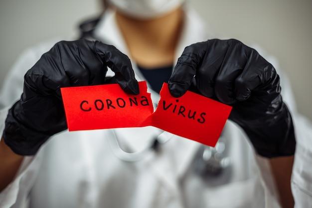 Kobieta lekarz rozdziera czerwony papier koronawirusa