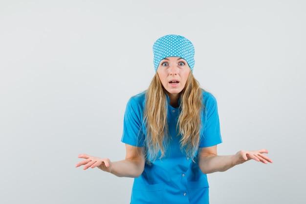 Kobieta lekarz rozkłada dłonie w zdziwionym geście w niebieskim mundurze