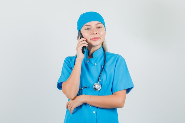 Kobieta lekarz rozmawia przez telefon komórkowy i uśmiecha się w niebieskim mundurze