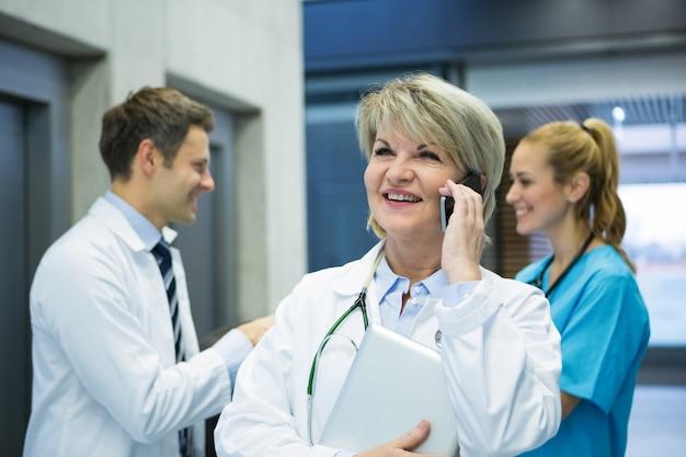 Kobieta lekarz rozmawia przez telefon komórkowy