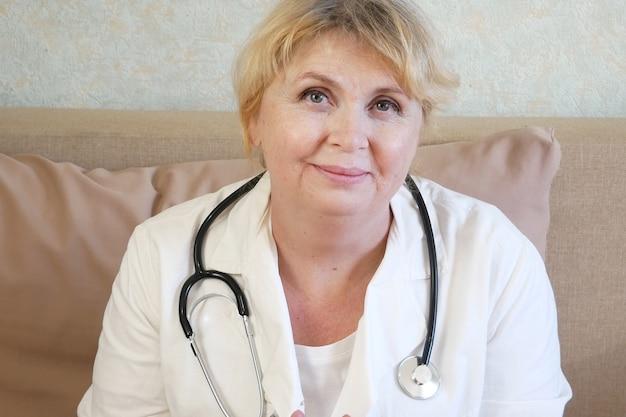 Kobieta lekarz siedzi i uśmiecha się. zbliżenie