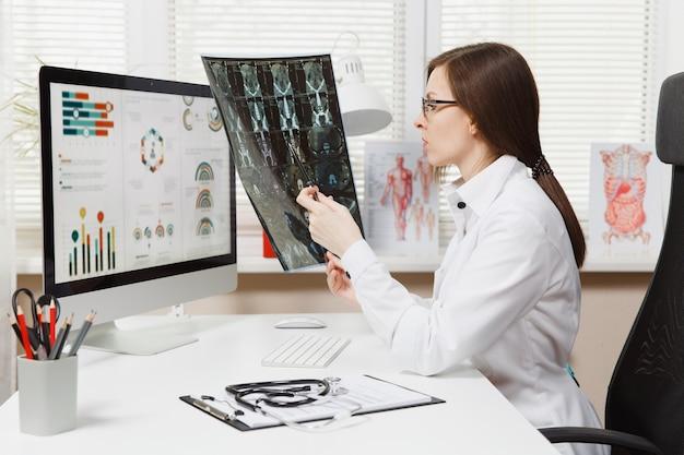 Kobieta lekarz siedzi przy biurku z komputerem, film rentgenowski mózgu przez obraz radiograficzny ct scan mri w jasnym biurze w szpitalu