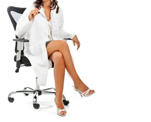 Kobieta lekarz siedzi ze skrzyżowanymi nogami. kopia przestrzeń.